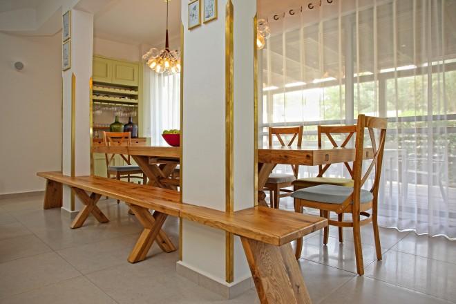 ספסל העץ חובק את העמוד ומאפשר את פינת האוכל הגדולה למרות העמוד התומך