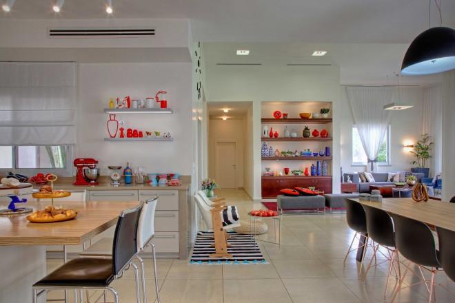 מבט מהמטבח לסלון חושף מוטיב חוזר של נגיעות צבע אדום