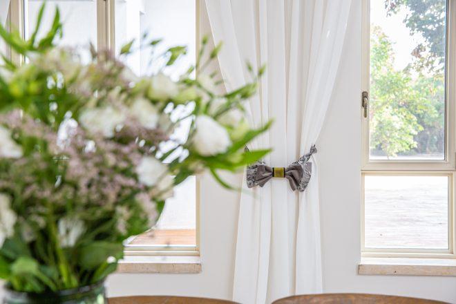 בד הפפיונים שעל הוילונות מהדהד את צבע וטקסטורות הפריחה