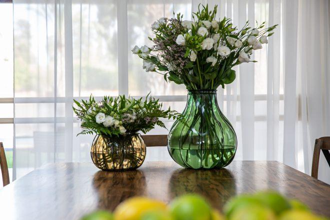 אגרטלים רחבים עם פרחים טריים המוחלפים מידי שבוע